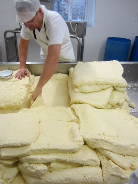 Slabs of cheese curds are stacked upon one another.