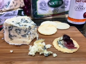 A tasty bite of Roquefort slathered on a Waterwheel cracker and topped with some Naturello Sour Cherry Preserves.